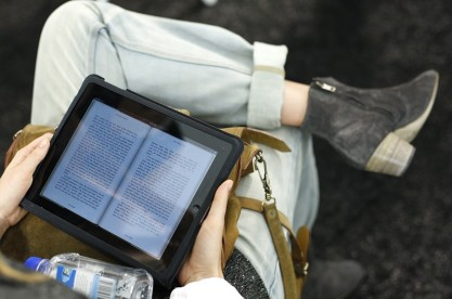 A model reads a book using an electronic device before the Lacoste Spring 2011 collection during New York Fashion Week