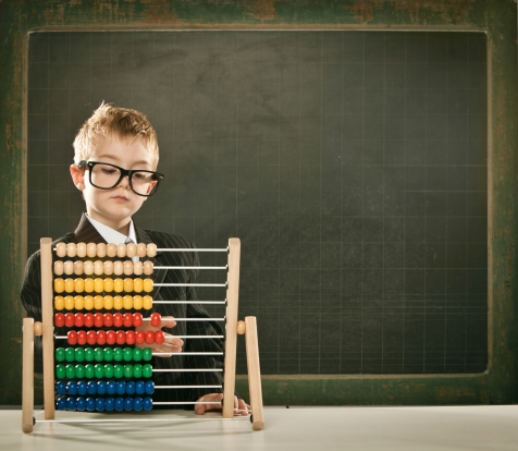 young serious scientist child with abacus and copyspace blackboa